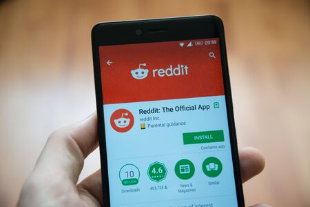 Los Angeles, november 2, 2017: Man hand holding smartphone with Reddit application in google play store