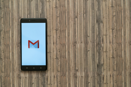 gmail: Los Angeles, USA, november 7, 2017: Gmail logo on smartphone screen on wooden background.