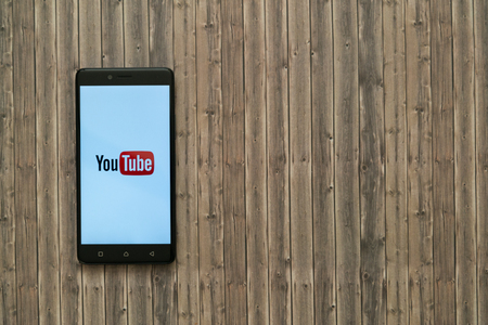 Los Angeles, USA, november 7, 2017: Youtube logo on smartphone screen on wooden background. Editorial