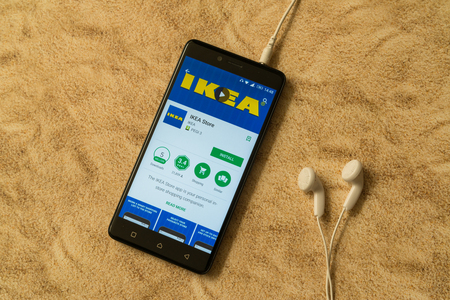 London, november 14, 2017: Ikea application in google play store on sandy background and earphones Editorial