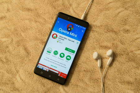 London, november 14, 2017: Opera mini application in google play store on sandy background and earphones