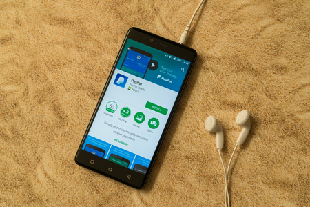 paypal: London, november 14, 2017: Paypal application in google play store on sandy background and earphones