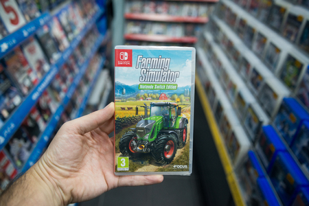 Bratislava, Slovakia, december 2, 2017: Man holding Farming simulator videogame on Nintendo Switch console in store Editorial