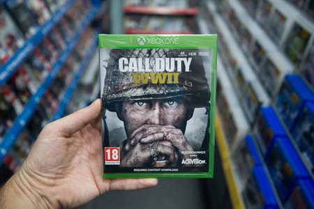 Bratislava, Slovakia, december 1, 2017: Man holding Call of duty world war II videogame on Microsoft XBOX One console in store