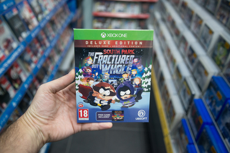 Bratislava, Slovakia, december 1, 2017: Man holding Southpark The fractured but whole videogame on Microsoft XBOX One console in store