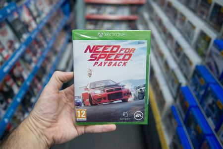 Bratislava, Slovakia, december 1, 2017: Man holding Need for speed payback videogame on Microsoft XBOX One console in store
