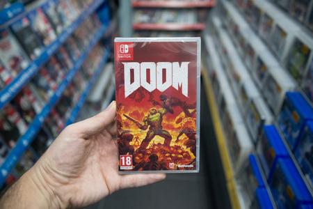 브라 티 슬라바, 슬로바키아, 2017 년 12 월 2 일 : 스토어의 Nintendo Switch 콘솔에서 Doom 비디오 게임을 들고있는 남자