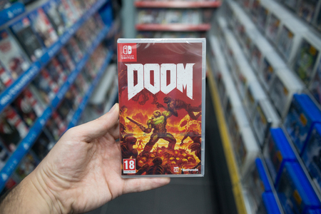 Bratislava, Slovakia, december 2, 2017: Man holding Doom videogame on Nintendo Switch console in store