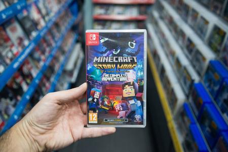 Bratislava, Eslovaquia, el 2 de diciembre de 2017: Sirva llevar a cabo el videojuego del modo de la historia de Minecraft en la consola del interruptor de Nintendo en tienda Foto de archivo - 91065637