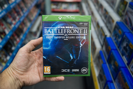Bratislava, Slovakia, december 1, 2017: Man holding Star wars battlefront 2 videogame on Microsoft XBOX One console in store Editorial