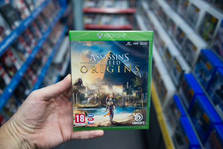 Bratislava, Slovakia, december 1, 2017: Man holding Assassins creed Origins videogame on Microsoft XBOX One console in store