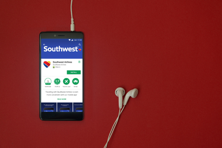 Los Angeles, January 11, 2018: Smartphone with Southwest airlines application in google play store on red background with earphones plugged in and copy space Editorial