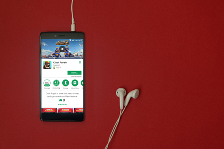 Los Angeles, January 11, 2018: Smartphone with Clash Royale application in google play store on red background with earphones plugged in and copy space