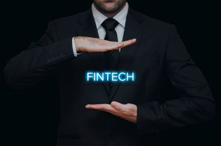 Businessman concept with fintech showing between his hands on black background