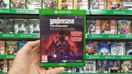 Bratislava, Slovakia, july 23, 2019: Man holding Wolfenstein Youngblood Deluxe Edition videogame on Microsoft XBOX One console in store