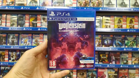Bratislava, Slovakia, July 23, 2019: Man holding Wolfenstein Cyberpilot VR videogame on Sony Playstation 4 console in store Editorial