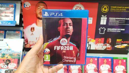 Bratislava, Slovakia, september 18 2019: Man holding Fifa 20 videogame on Sony Playstation 4 console in store Redakční