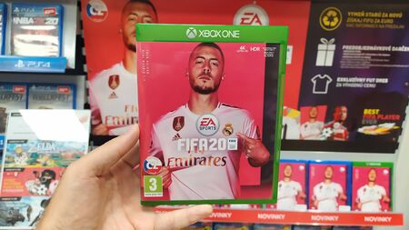 Bratislava, Slovakia, october 2, 2017: Man holding NHL 2020 videogame on Microsoft XBOX One console in store