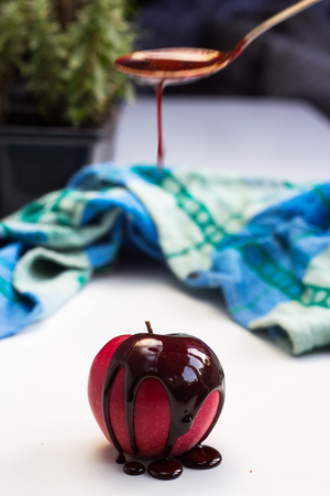 molted: Chocolate drop on red apple fruit. Chocolate motion.