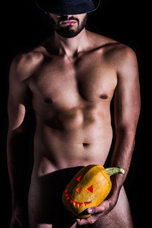 männer nackt: Nackter Mann mit Hut Betrieb gruselig geschnitzt Halloween-Kürbis auf schwarzem Hintergrund
