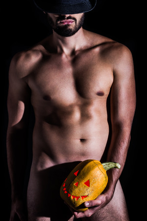 hat nude: Naked man with hat holding creepy carved halloween pumpkin on black background