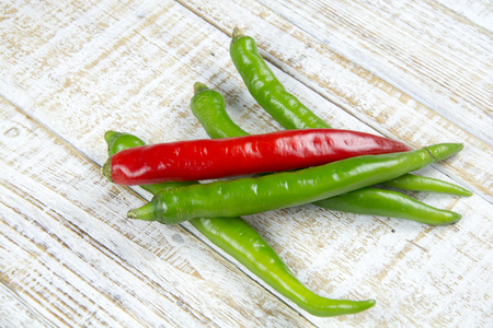 Green and Red chili pepper isolated on a wood background Stock Photo
