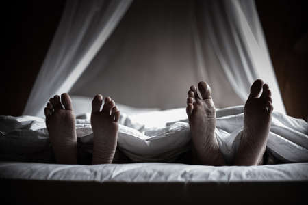 Photo of couple's feet on their bed room. They commit suicide after they fail in their lives.