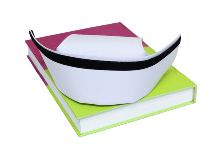 nurse hat: An isolated nurse hat placed on textbook
