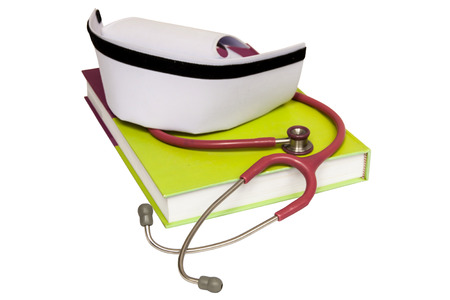 An isolated nurse hat on textbook and stethoscope Stock Photo