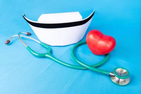 nurse cap: Estetoscopio, sombrero de la enfermera y el corazón de cerámica roja en tela azul.