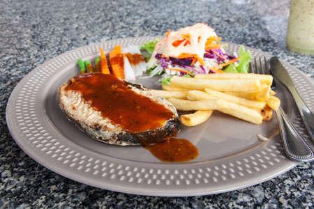 fish vendor: Steak king mackerel and vegetables salads, potato fried. Stock Photo