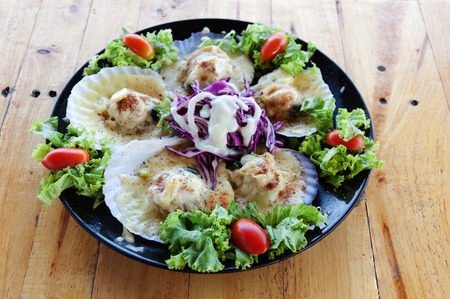 prepared shellfish: Baked Scallops with Cheese in black dish on wood table.