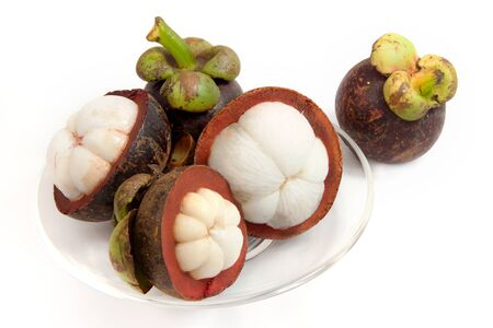 sweet segments: mangosteen fruit split on a clear glass plate on isolated white with clipping path a tropical fruit with sweet juicy white segments of flesh inside a thick reddish-brown rind. Stock Photo