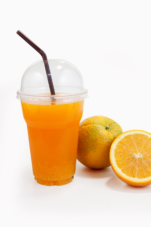 clear path: Orange juice in plastic clear cup and orange fruit on isolated white with clipping path Stock Photo