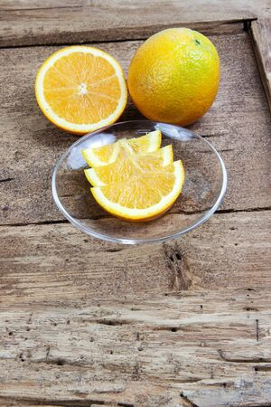 bonanza: Orange sliced in half and thinly sliced on old table wood Stock Photo
