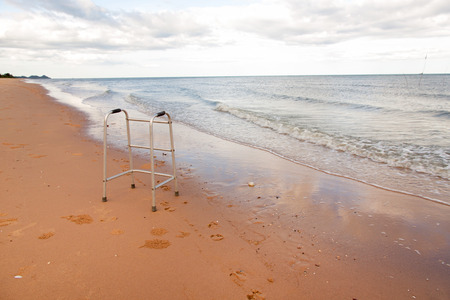 freedom leisure activity: walker on sand beach. convey in meaning the relax tourist attractions of the elderly.
