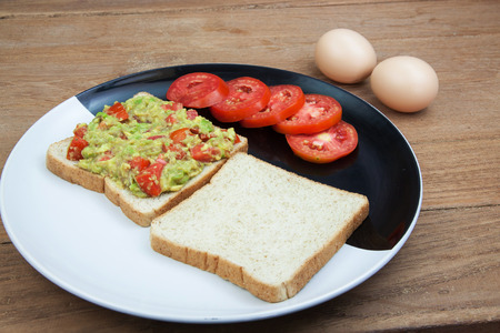 whole wheat: Avocado sauce and whole wheat in black dish on wood