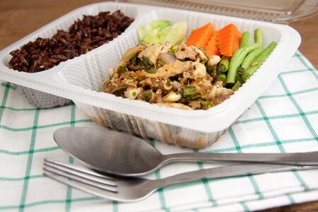 chicken salad: Spicy minced chicken salad and brown rice thai cuisine put in a modern plastic box
