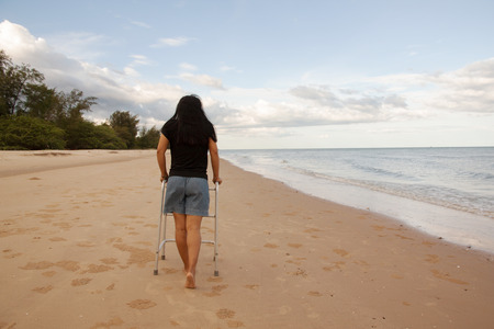 woman use walker on sand beach. convey in meaning the relax tourist attractions of the patient Stock Photo