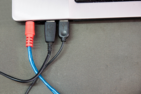 computer peripheral: USB cable connected to a notebook computer. and cable channels and external speakers.