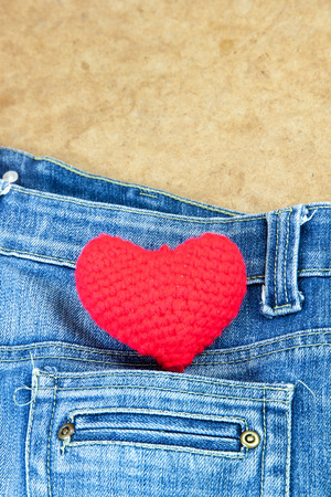 love abstract: Crochet heart red color on blue Jeans