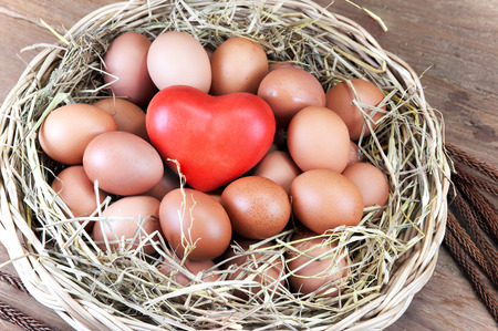 love image: Red heart and eggs in a basket with straw secondary on wood table.