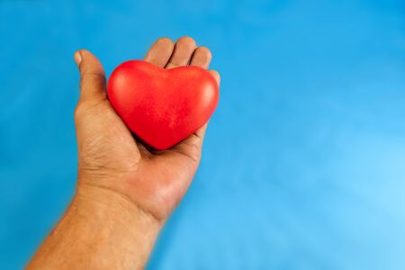 dating strategy: handle with heart care. Hand holding a red heart. isolated blue background with clipping Paths