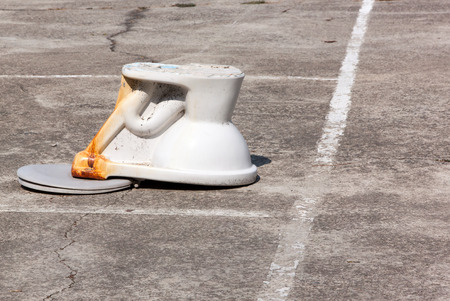 a toilet stool: flush toilet upside down on outdoor cement. concept do not let anyone take only a stool, sputum, urine, spit filth into the pond or in the  public