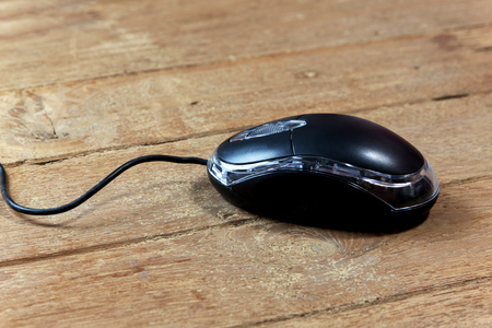 wired: Black wired computer mouse on wood table Stock Photo