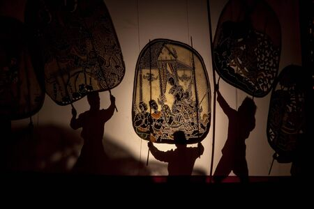 khanon: RATCHABURI THAILAND - APRIL 14, 2015: The Cowskin shows a man holding a stencil pattern. Moving Cowskin the light to shadow play. The musical atmosphere and read a poem composed.