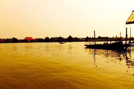 long tail: Long tail wood boat engine in the river at dawn with golden light. Sunrise with silhouette
