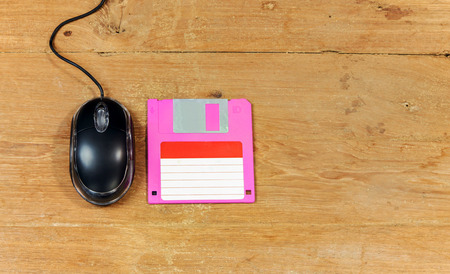 optical disk: Black wired computer mouse and floppy disk on wood table
