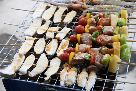 kebob: chicken shish kebab on bbq grill in sauce on skewers with tomatoes and peppers. shrimp and eringii mushroom grill. Stock Photo