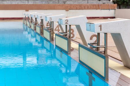 start to cross: blue water wave in swimming pool reflects with sunlight , blue tile ceramic to swimming race and water sports.